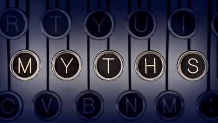 Close-up van oude typemachine toetsenbord met bekraste chrome sleutels die spellen MYTHS Verlichting en de focus zijn gericht op MYTHS