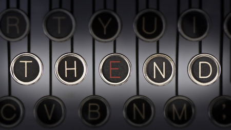 Close up of old manual typewriter keyboard with scratched chrome keys that spell out  THE END   Both words share the letter,  photo