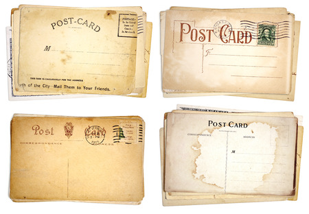 Four stacks of blank, heavily aged post cards from early 1900s   Isolated on white  Imagens