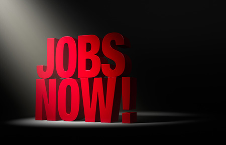 angled: Angled spotlight reveals a bold, red JOBS NOW! on a dark background. Stock Photo