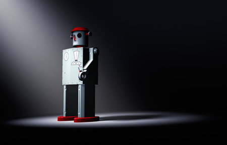 A 1950s style tin toy robot stands alone on a dark background dramatically lit from the front by a spotlight.