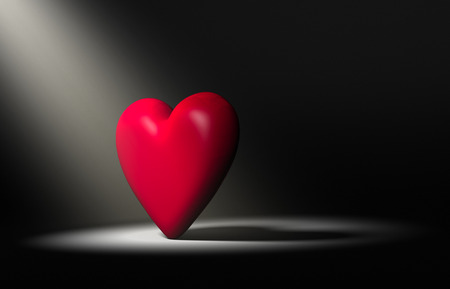 Large, red heart stands forward in a bright spotlight on a dark background. Фото со стока