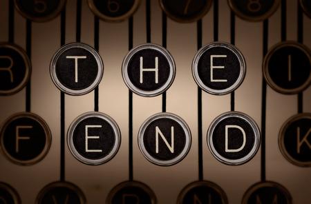 """Sepia-afgezwakt close-up van het oude typemachine toetsenbord met krassen chroom sleutels die spellen """"THE END"""" op twee rijen. Verlichting en de focus zijn gericht op """"het einde"""" toetsen. Stockfoto"""