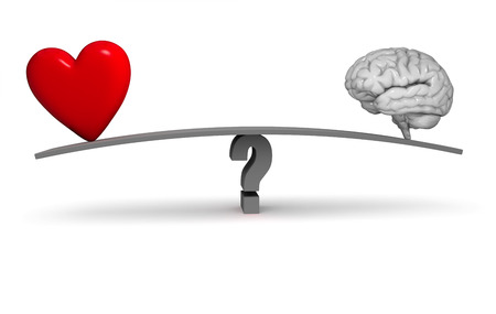 A bright, red heart and gray brain sit on opposite ends of a dark gray board balanced on a gray question mark. Isolated on white. Stock Photo