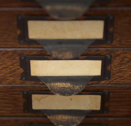 tarnished: Stack of three old, oak flat file drawers with blank yellowed tags in tarnished brass label holders. Shallow DOF with focus and lighting on the middle drawer.