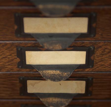 tarnished 황동 레이블 보유자에 빈 yellowed 태그와 세 오래 된, 오크 플랫 파일 서랍의 스택. 포커스와 중앙 서랍 조명 얕은 DOF.