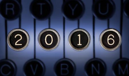 """""""2016""""형태의 긁힌 크롬 키가있는 오래된 타자기 키보드의 이미지. 조명과 초점은 """"2016""""을 중심으로 이루어집니다."""