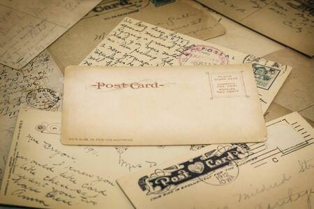 Close up of vintage, handwritten postcards from the 1920s and earlier, with a blank postcard in the center. Viewed at an hangle with shallow depth of field.