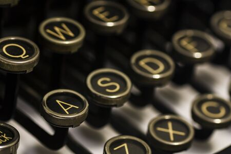 Close Up of black antique typerwriter keyboard with yellowing letters. Shallow DOF