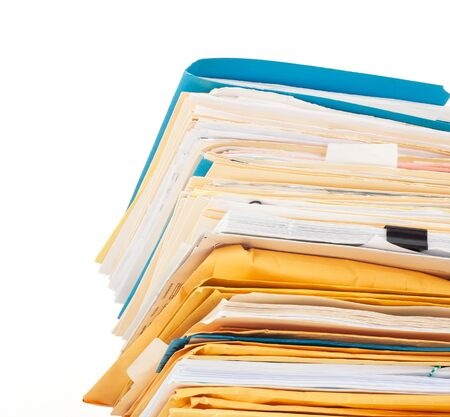 Looking up at an intimidating stack of well worn file folders, manilla envelopes, and papers isolated on white.