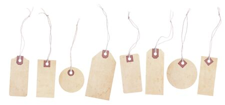 A collection of eight old yellowing paper tags. Each tag has a string tie and is blank with room for text or images. Isolated on white 写真素材