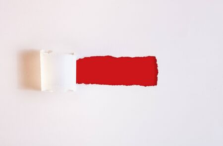Close up of a torn strip of white paper, curling to the side and creating a hole revealing a plain red background.
