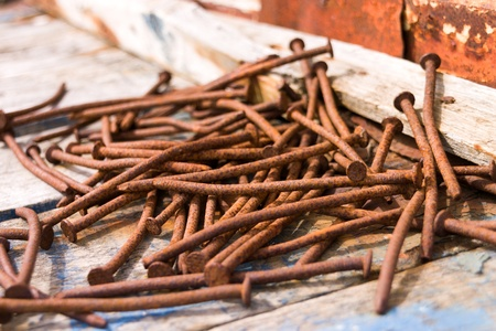 Rusted nails on a wooden ground
