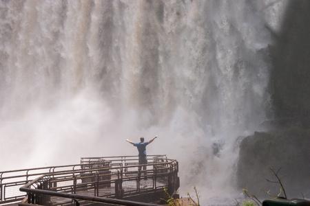 Man standing close to the Iguacu Falls hands up Power symbol Stock Photo - 18382713