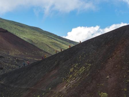 Trekking people in windsuits in a lane descending