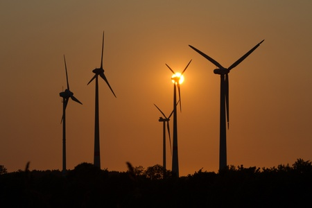 Wind engines in rural scene with setting sun