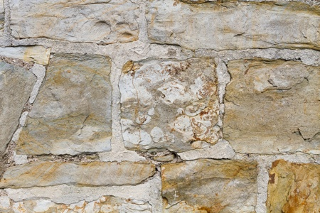 Stone wall outside with yellow stones and cement