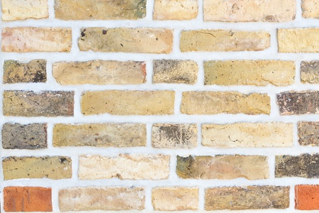 Brick wall with yellow and red stones