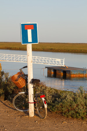 Bycicle leaning on a dead end sign by the sea