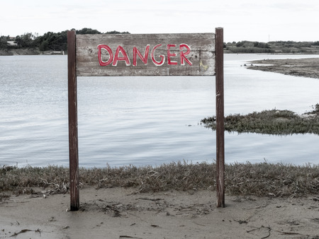 Danger sign on a riff by the sea