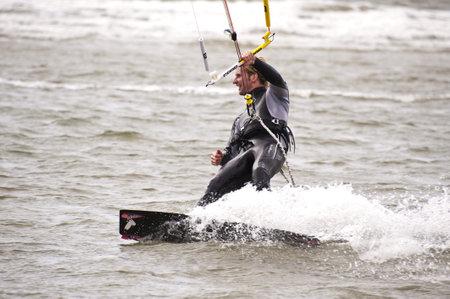 kiter: ST. PETER-ORDING, GERMANY - JULY 22: Professional  kite-surfer Karsten Koschewski, Germany,  demonstrating his ability on the Palmolive Kitesurf Worldcup 2010 in St. Peter-Ording, July 22, 2010 in St. Peter-Ording, Germany Editorial