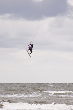 ST. PETER-ORDING, GERMANY - JULY 24: Professional kite-surfer demonstrating his ability on the Palmolive Kitesurf Worldcup 2010 in St. Peter-Ording, July 24, 2010 in St. Peter-Ording, Germany Stock Photo - 8449800