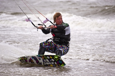 kiter: ST. PETER-ORDING, GERMANY - JULY 24: Professional kite-surfer Fabian Bertschat, Germany, demonstrating his ability on the Palmolive Kitesurf Worldcup 2010 in St. Peter-Ording, July 24, 2010 in St. Peter-Ording, Germany