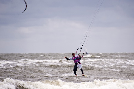 kiting: ST. PETER-ORDING, GERMANY - JULY 24: Professional kite-surfer demonstrating his ability on the Palmolive Kitesurf Worldcup 2010 in St. Peter-Ording, July 24, 2010 in St. Peter-Ording, Germany