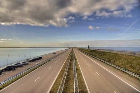 street at the ijssel lake in the netherlands with cloudy sky (hdr)