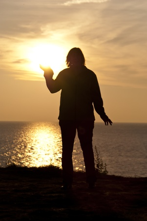 Woman holding the sun on sunset photo