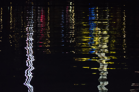 mirroring: Reflective Night Lights on a Water Surface on the Kiel Week Festival in Germany