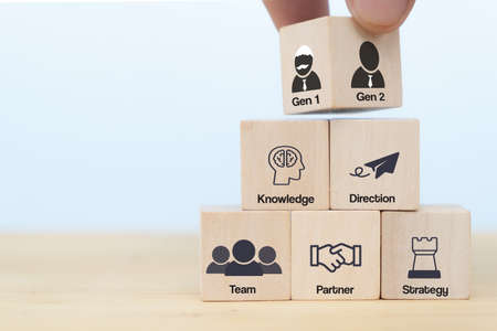 business hand man put arranging on wooden cube block that family or company Succession business concept from old generation to next generation. transfer Knowledge, Direction, Team, Partner, Strategy Foto de archivo