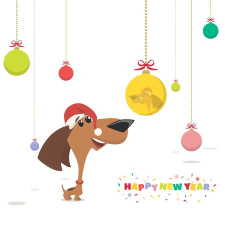 christmas card, puppy looks at a Christmas ball. Фото со стока