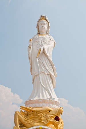 kuan yin on dragon statue and blue sky