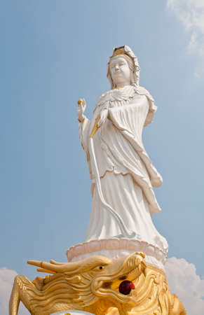 kuan yin on dragon statue and blue sky photo