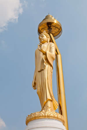 gold buddha standing and blue sky  photo