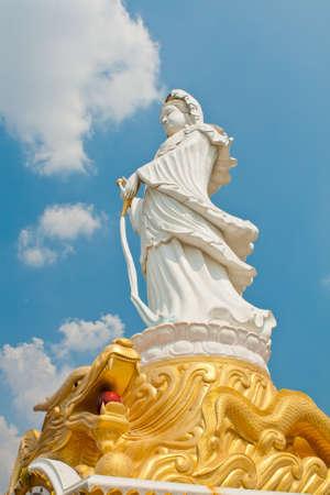 kuan yin on dragon statue and blue sky