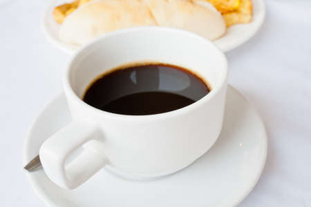 Coffee in a white cup and bread photo