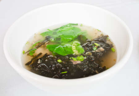 Thai pork soup and seaweed in white bowl photo
