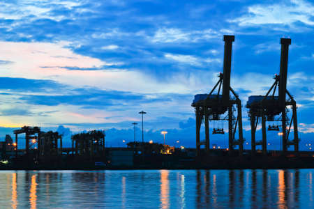 Containers and cranes at the port at sunrise in Bangkok, Thailand  photo