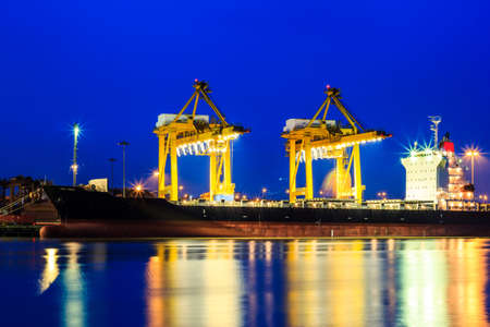 Container and crane in shipyard at dusk for cargo Goods and Logistic in harbor Stock Photo