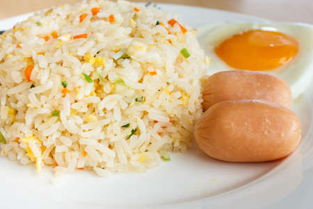 Fried rice and egg with sausage on a white dish photo