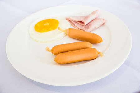 Breakfast style ham and sausage with egg on white plate photo