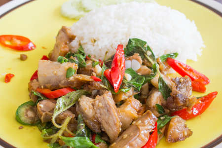 Basil fried pork with rice on the dish photo