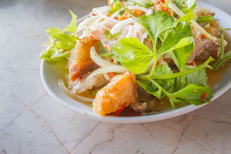 Spicy salad fish in a dish on table