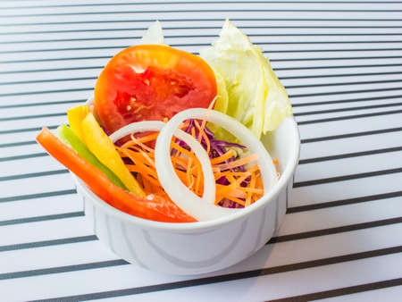 Vegetable salad in a white bowl on table