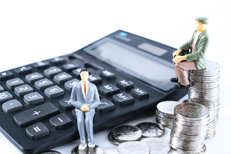 A businessman who thinks or makes a decision with a calculator and a coin. Banque d'images