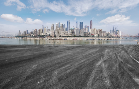 The empty asphalt road is built along modern commercial buildings in Chinas cities.