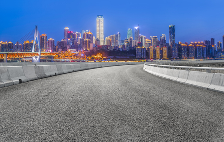 The empty asphalt road is built along modern commercial buildings in China's cities.