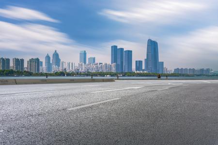 Asphalt pavement and Suzhou Jinji Lake skyscraper
